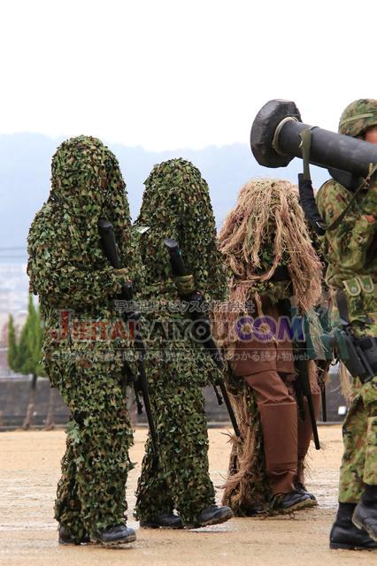 狙撃銃を手に偽装網を着用した陸上自衛隊員。